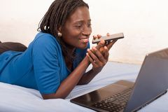 Young smiling woman talking on mobile phone in bed royalty free stock photos