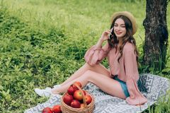 Young smiling woman talking on smartphone while resting on blanket with wicker basket full of apples. In park stock image