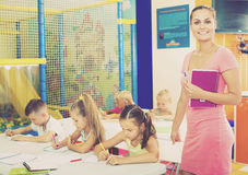 Young smiling woman teacher standing with textbook. Young smiling women teacher standing with textbook in school class with kids Royalty Free Stock Photo