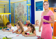 Young smiling woman teacher standing with textbook. Young smiling women teacher standing with textbook in school class with kids Royalty Free Stock Images