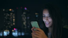 Young Smiling Woman Texting on Mobile Phone at Night in City. 4K. Attractive Mixed Race Girl Using Smartphone with. Blurred Blue Bokeh Street Lights Background stock video