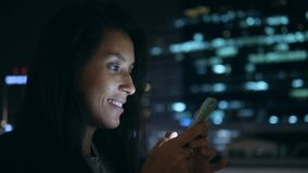 Young Smiling Woman Texting on Mobile Phone at Night in City. 4K. Attractive Mixed Race Girl Using Smartphone with. Blurred Blue Bokeh Street Lights Background stock video footage