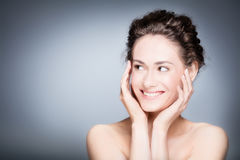 Young smiling woman touching her healthy, fresh face. Skin care. Young smiling woman touching her smooth, healthy, fresh face. Portrait close up on grey stock image