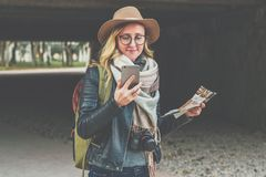 Young smiling woman tourist in hat stands on street and uses smartphone while holding destination map in her hand. Young smiling woman tourist in hat and Stock Images