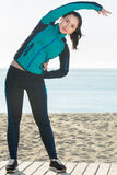 Young smiling woman training on beach by sea Royalty Free Stock Image
