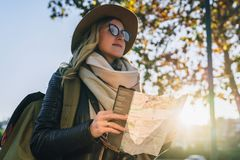 Young smiling woman travels in hat and eyeglasses stands on city street, holding map in her hands.Hipster girl walks. Sunny autumn day, backlight. Young Royalty Free Stock Image