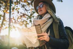 Young smiling woman travels in hat and eyeglasses stands on city street, holding map in her hands.Hipster girl walks. Sunny autumn day, backlight. Young Royalty Free Stock Photos