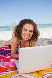 Young smiling woman typing on her laptop while lying on the beac Royalty Free Stock Images