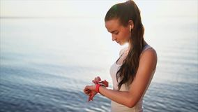 Young smiling woman using her smartwatch touchscreen wearable technology outside. Young smiling woman using her smartwatch touchscreen wearable technology device stock footage