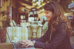 Young smiling woman using laptop at cafe. Royalty Free Stock Photo