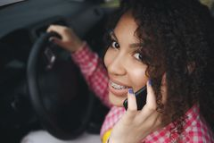 Young smiling woman using phone while driving her car royalty free stock images