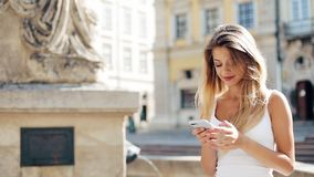 Young smiling woman using smartphone in the European city. She sits behind the fountain on the square. Beautiful girl. Young smiling woman using smartphone in stock video footage