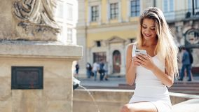 Young smiling woman using smartphone in the European city. She sits behind the fountain on the square. Beautiful girl. Young smiling woman using smartphone in stock video