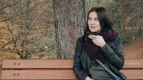 Young Smiling Woman Using Smartphone Sitting On Bench In Park. Beautiful European Girl Making Voice Message On Phone. Young Smiling Woman Using Smartphone stock footage