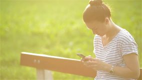 Young smiling woman using smartphone sitting on bench in park. Beautiful european girl texting on phone stock footage