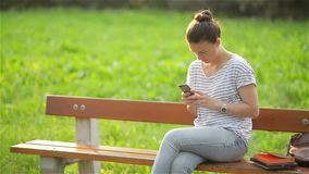 Young smiling woman using smartphone sitting on bench in park. Beautiful european girl texting on phone stock video