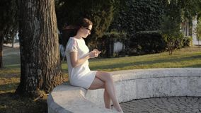 Young smiling woman using smartphone sitting on bench in park at the sunset. Beautiful European girl texting on phone stock footage