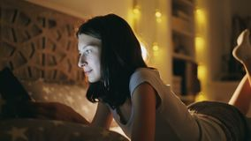 Young smiling woman using tablet computer for sharing social media lying in bed at home at night. Time stock footage