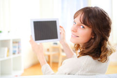 Young smiling woman using a tablet on a sofa Stock Photo