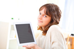 Young smiling woman using a tablet on a sofa Royalty Free Stock Photography