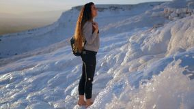 Young woman walking in Pamukkale terraces. Young smiling woman walking in Cotton Castle limestone terraces in Pamukkale Turkey during beautiful sunset stock video footage