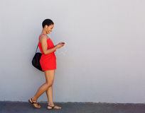 Young smiling woman walking with mobile phone and earphones. Full body side portrait of young smiling woman walking with mobile phone and earphones Stock Images