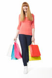 Young, smiling woman walking with shopping bags Stock Photo