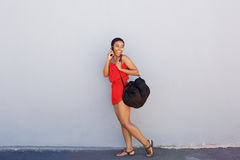 Young smiling woman walking and talking on cellphone. Full body side portrait of young smiling woman walking and talking on cellphone Stock Photo