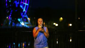 Young smiling woman on the waterfront with headphones listening to music from the phone and writing a message against stock footage