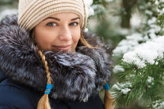 Young smiling woman wearing blue hooded real fur trim down coat enjoying view in winter forest outdoors. Nature cold season freshn. Ess concept Royalty Free Stock Images