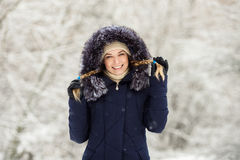 Young smiling woman wearing blue hooded real fur trim down coat enjoying view in winter forest outdoors. Nature cold season freshn Stock Photography
