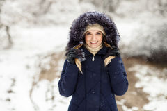 Young smiling woman wearing blue hooded real fur trim down coat enjoying view in winter forest outdoors. Nature cold season freshn Stock Photo