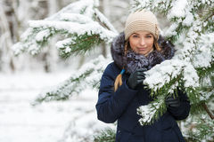 Young smiling woman wearing blue hooded real fur trim down coat enjoying view in winter forest outdoors. Nature cold season freshn Royalty Free Stock Images