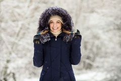 Young smiling woman wearing blue hooded real fur trim down coat enjoying view in winter forest outdoors. Nature cold season freshn Royalty Free Stock Photos