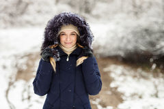 Young smiling woman wearing blue hooded real fur trim down coat enjoying view in winter forest outdoors. Nature cold season freshn Stock Photos
