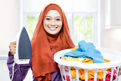Young smiling woman wearing hijab holding iron and carrying laun Stock Photos
