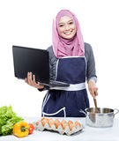 Young smiling woman wearing hijab on laptop PC cooking making fo stock photography