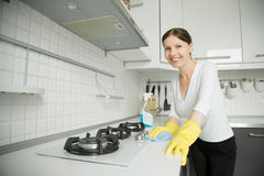 Young smiling woman wearing rubber gloves cleaning the stove Royalty Free Stock Images