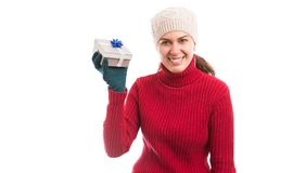Young smiling woman wearing warm clothes and holding a gift royalty free stock image