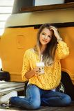 Beautiful smiling woman is wearing yellow sweater drinking coffee latte near old retro bus. Young smiling woman is wearing yellow knitted sweater and jeans is Royalty Free Stock Images
