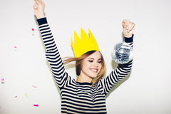 Young smiling woman on white background celebrating party, wearing stripped dress and yellow paper crown, happy dynamic Royalty Free Stock Photo