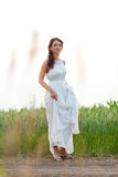 Smiling woman in white dress standing in field Royalty Free Stock Photography