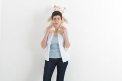 Young smiling woman in white shirt and jeans with short hair who is carrying plush toy cat on her shoulders. Young smiling woman in white shirt and jeans with Royalty Free Stock Image