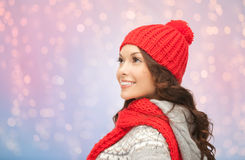Young smiling woman in winter clothes. Winter holidays, christmas and people concept - smiling young woman in red hat and scarf over rose quartz and serenity Royalty Free Stock Images
