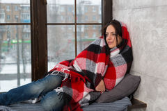 Young smiling woman wrapped in a blanket while lying down on the. Windowsill in the living room stock images