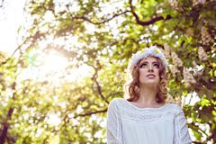 Young smiling woman with a wreath of chamomiles on her head in the park Stock Photography