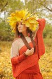 Young smiling woman with wreath of maple leaves on a head, outdoor portrait. In autumn park stock photography