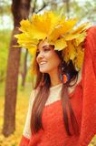 Young smiling woman with wreath of maple leaves on a head, outdoor portrait. In autumn park royalty free stock image