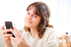 Young smiling woman writing a text Stock Photos