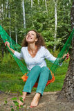 Young smiling woman with yellow flower sits in hammock. Young smiling woman with yellow flower in her hand sits in hammock and look at the sky royalty free stock photography